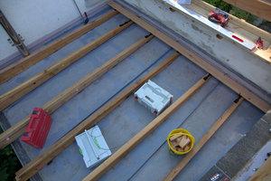 Das erste Brett liegt auf der Unterkonstruktion auf dem kleinen Dach. Es wird ausgemittelt, der Abstand vom Rand beträgt etwa 10mm