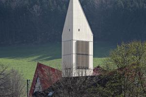 Schon von Weitem ist die helle Holzkonstruktion des Turms mit dem spitz zulaufenden Dach sichtbar