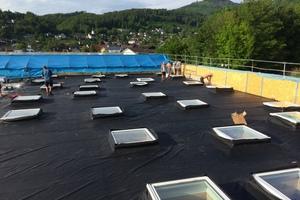 Die vorkonfektionierte EPDM-Dachplane ist ausgelegt und wird mit Kontaktkleber an den Aufsatzkränzen befestigt