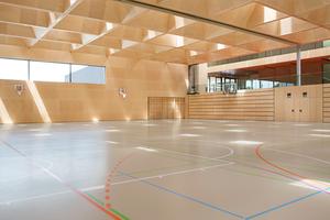 Insgesamt 56 Flachdachfenster belichten gemeinsam mit dem Lichtband in der Fassade das Spielfeld der neuen Sporthalle