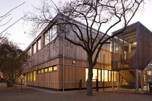 Obergeschoss und Erdgeschoss des Schulgebäudes sind einheitlich mit einer Lärchenholzschalung verkleidet<br />