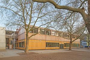 Das eingeschossige Gebäude der Erich-Kästner-Grundschule in Darmstadt wurde 2018 aufgestockt. Nun wurde auch die Fassade des Erdgeschosses mit einer Holzschalung versehen