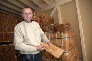 Zimmerer Egon Frick zeigt die Lärchenholzschindeln, mit denen die Fassade beplankt wurde