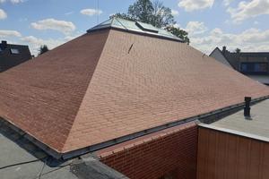 Blick auf eines der fertiggestellten Dächer: Die Klinkersteine bilden eine einheitliche Ebene. Auf dem Dach wurde ein Lichtband in Walmdachform eingebaut