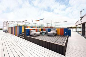 Die bunte, leicht erhöht gelegene Dachterrasse wird eingerahmt von weißen Terrassendielen<br />