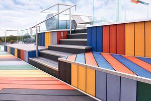 Die Dachterrasse wurde mit bunten Holzverbunddielen gestaltet. Profile aus Stahl bilden die Übergänge zwischen den Sitz- und Wandflächen