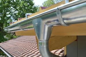Die mithilfe des Rinnenhaken-Sets von Zambelli fertig montierte Dachrinne mit Stutzen und Rinnenbogen<br />