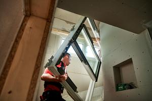 Der Transport des Fensterrahmens durch das Treppenhaus ist möglich, kann aber knifflig werden. Kräfteschonender ist die Verwendung eines Krans und der Velux Hebevorrichtung