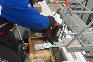 Ein Sifatec-Mitarbeiter montiert eine Halteplatte des Seitenschutzsystems am Dachrand