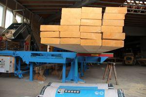 Auf dem hydraulischen Hubtisch an der Maschine (rechts im Bild) können Holzpakete aufgesetzt und auf die gewünschte Höhe gehoben werden <br />