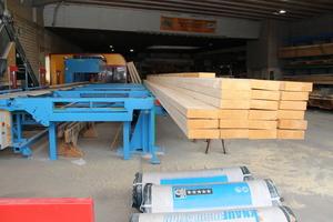 Bei geöffnetem Hallentor lassen sich mit der neuen Abbundmaschine bis zu 16 m lange Hölzer bearbeiten