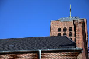 Das Dach der St. Josephskirche nach der Sanierung. Im Vordergrund das Hauptdach, eingedeckt mit rautenförmigen Dachziegeln, im Hintergrund der Kirchturm mit goldenem Kreuz