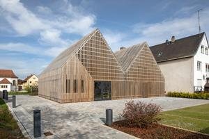 Für die neue Bücherei in Gundelsheim wurde ein ehemaliges Bauernhaus mit Stall umgenutzt und um einen Neubau erweitert, der eine umlaufende Holzverkleidung an Dach und Fassade erhielt<br />