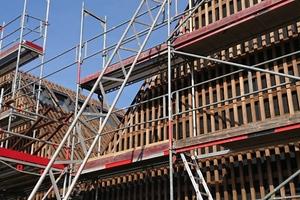 Die Fassadenverkleidung aus Thermoholzlamellen zieht sich von der Fassade über das Dach des Gebäudes