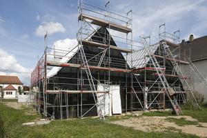 An den Außenwänden wurden schwarze Fassadenbahnen verlegt, die den Hintergrund für die Holzlamellenverkleidung bilden
