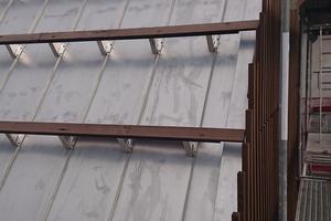 Schneefangklemmen auf Edelstahlbechen nehmen die Unterkonstruktion für die Lamellenverkeidung auf