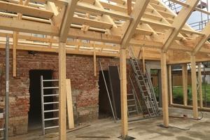 Zwischen den Satteldächern des ehemaligen Stalls und des Neubaus liegen die Doppelrahmenbinder des Daches auf Mittelstützen auf