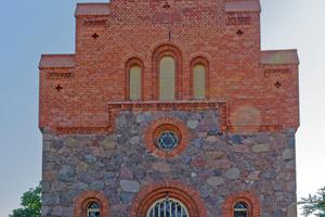 Das westseitige Portal der Kirche ist mit einem gestaffelten Giebel gestaltet, auf der obersten Zinne steht ein Kreuz<br />