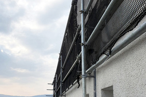 Der Seitenschutz wurde mit vier Rohren in der Waagerechten sowie durchgehenden Netzen versehen, um bestmöglich vor Absturz zu sichern und ein Herabfallen von Gegenständen zu verhindern.<br />