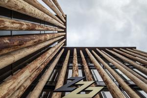 Die Baumstämme an der Fassade verleihen dem Neubau eine rohe und naturnahe Optik