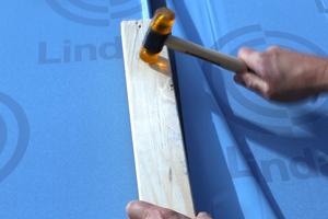 Die Klick-Verbindung wird mit einem Hammer gefestigt. Dabei sollte ein Schutzklotz untergelegt werden