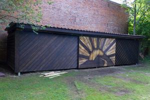 In der mittleren Front des 20 m² großen Unterstandes wurden zwei Schiebetorelemente in Form einer Sonne integriert