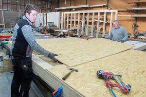 Vorfertigung der Holzrahmenwände und Beplankung mit OSB-Platten bei der Adams Holzbau-Fertigbau GmbH in Niederzissen