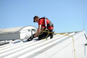 Bei Dacharbeiten ist auf eine sichere Verbindung zwischen dem Auffanggurt und dem Anschlagpunkt, an dem sich der Monteur anschlägt, zu achten