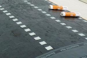 Nach Verlegen der Dämmplatten trugen die Dachdecker ein Bitumendeckanstrich auf. Die Dachkrallenplatten werden dann durch Druck und Anflämmen eingepresst