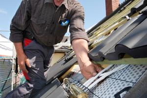 Einstecken der Schläuche in unteren Kollektor: Die Solarkollektoren werden fast wie herkömmliche Dachsteine verlegt. Das Leitungsnetz ist zwischen Trag- und Konterlatte verborgen. Die Unterdeckungsbahn (Empfehlung: eine Folienunterdeckbahn) und die Dämmung bleiben unberührt.