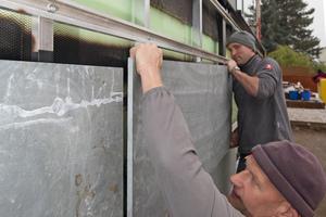Zwei Mann befestigen die Schiefersteine auf der Unterkonstruktion aus Aluminium. Auf der Rückseite sitzen vier Halterungen, so genannte eingeschraubte Hinterschnittanker