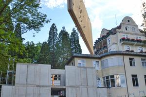 Die Wandteile wurden beim Aufbau über das bestehende Gebäude hinweg gehoben⇥Foto: Haas Fertigbau