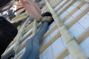 Auf dem Dach schließt der Handwerker das Wellrohr an und führt zwei Leitungen durch das Dachpaket. Dazu gehören auch alle erforderlichen Nebenarbeiten wie die Anbringung der Dichtmanschetten. Unter dem Dach führt der Installateur die Leitungen zur Wärmepumpe.
