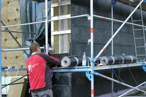 Die Schieferplatten werden an Schienen an der Fassade montiert