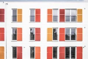 Die einladenden Farben der Fensterläden gestalten die FassadeFoto: Meuer Architekten