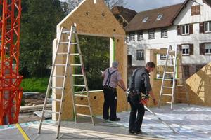 """Für den Neubau stellen die Zimmerleute neue Holzrahmenwände auf<span class=""""bildnachweis"""">Foto: Partner und Partner Architekten</span>"""