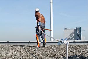 """Ein Dachdecker bei der Dachüberprüfung mit der Persönlichen Schutzausrüstung gegen Absturz (PSAgA)<span class=""""bildnachweis"""">Foto: Skylotec</span>"""