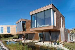 Der auskragende Holzbau hat mehrere breite und hohe Glasscheiben und öffnet sich mit den Glasfronten zum Tal