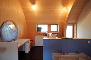 """In den Räumen der Kinderkrippe bestehen die Wand-Decken der Außenwände aus massiven Profil-Holz-Elementen, die der Krümmung der Binder folgen<span class=""""bildnachweis"""">Fotos: Thomas Wieckhorst</span>"""