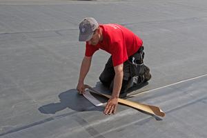 Obere Dachbahn zurückklappen. Schutzpapier aus dem Nahtbereich herausziehen. Obere Bahn per Hand andrücken