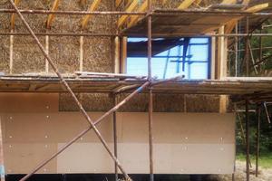 """Die Strohballen wurden zwischen aufrechten Ständern eingestapelt beziehungsweise eingeklopft. Mit einer Holzweichfaserplatte wird die äußere Schicht ausgebildet<span class=""""bildnachweis"""">Fotos (2): Oximoron</span>"""