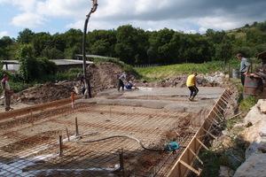 Bauarbeiter gießen das Betonfundament für den Neubau<br />