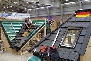 Rechts das vom deutschen Dachdeckerteam eingedeckte Gratdach. Links baut Volker Pohlmeyer gerade ein Dachfenster ins Kehldach ein