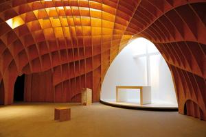 """Das Holzgewölbe öffnet sich zum Altar hin zu einer weißen Nische, die von den verglasten Innenseiten der Türme indirekt beleuchtet wird<span class=""""bildnachweis"""">Foto: Helen Schiffer</span>"""