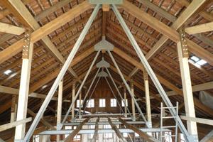 """Links: Der neue Dachstuhl, verstärkt mit neuen Mittelpfetten, Pfosten und 15 m langen Stahlstreben <span class=""""bildnachweis"""">Foto: Partner und Partner Architekten</span>"""