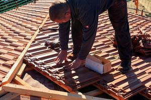 """Festdrücken des nachfolgenden Dachziegels in die im Kopfbereich des darunterliegenden Ziegels verschraubte """"Sturmfix""""-Klammer"""