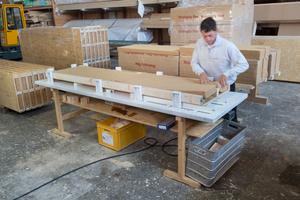 """Auf einem speziellen Fertigungstisch werden die Wandelemente produziert. Hier wird die Kerndämmung """"Kronoply flex"""" eingelegt"""