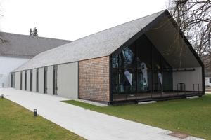 Der große Vortragssaal eine mit Lärchenholzschindeln bekleidete Holzkonstruktion, die an das Haus 6 der ehemaligen Kaserne andockt <br />