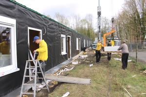 Ein Handwerker verklebt die Fassadenfolie, die anderen laden eine Palette mit Gipskartonplatten ab