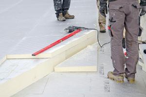 """Wegen der großen Dachfläche wurden zwei gegenläufige geneigte Dachhälften mit diagonalem """"First"""" realisiert. Die Schnur zwischen den beiden Mitarbeitern rechts markiert die Firstlinie"""